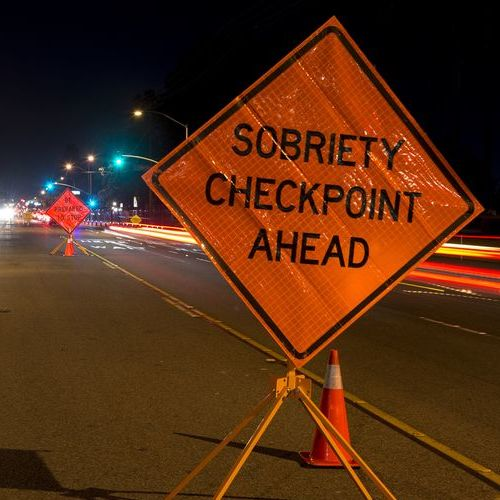 A notification of a sobriety checkpoint is pictured on a busy highway at nighttime.