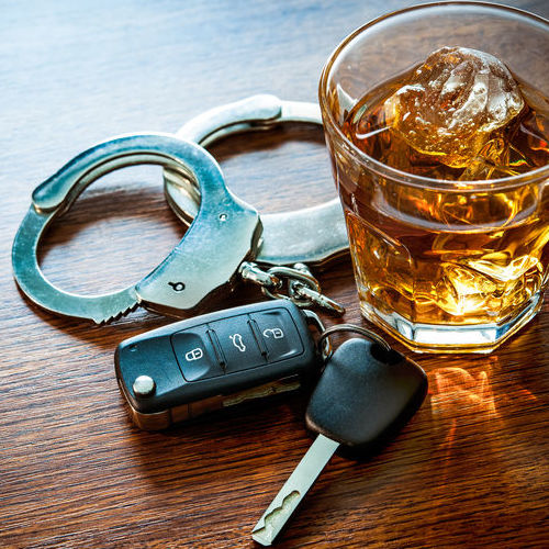 A shot of whiskey, a pair of smart car keys, and a pair of handcuffs rest on a table.