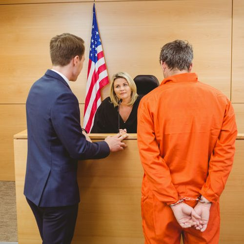 A Picture of a Lawyer and Judge Talking with a Man Standing Next To Them.