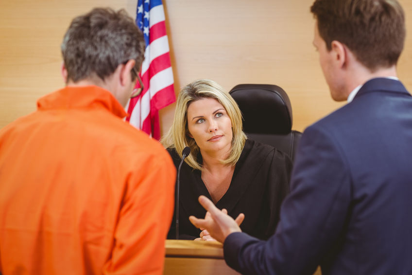 A Picture of a Lawyer and a Man in an Orange Jumpsuit Talking To a Judge.