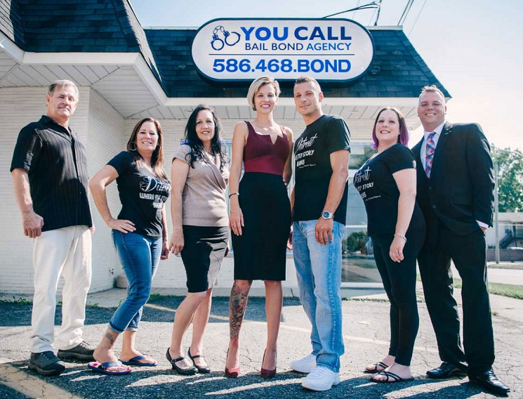 A Picture of Seven People Standing Outside in Front of a Building with a You Call Bail Bond Agency Sign.