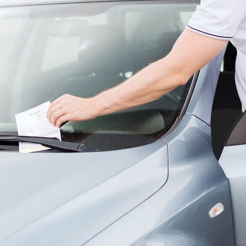 A Man Grabbing a Ticket Off of a Car Windshield