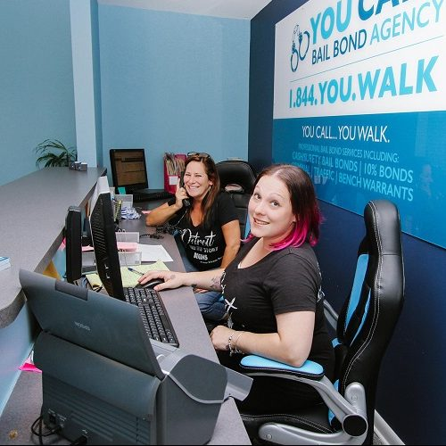 A Picture of Two Women Sitting at a Front Desk of an Office